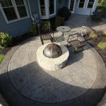 A fire pit sits on top of a stamped concrete patio