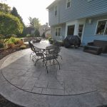 A dining table sits on a decorative concrete patio