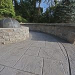 A fire pit and seating wall on a stamped concrete patio