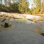 A pool surrounded by a stamped concrete patio and landscaping