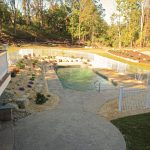 Landscaping and a patio surround a pool