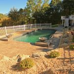 A pool surrounded with stamped concrete and landscaping