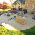 A large stamped concrete patio with an outdoor kitchen and fire pit