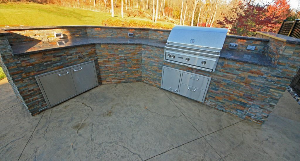 A Two Tier Decorative Concrete Patio With An Outdoor Kitchen And Fire Pit