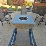 A square gas fired fire pit with a blue stone cap stone