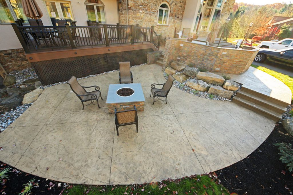 A stamped concrete with a gas powered fire pit
