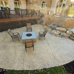A large fire pit area on a seamless textured concrete patio